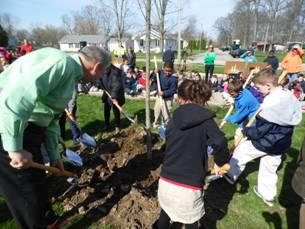 Fort Wayne City Councilman Mitch Harper and students plant a tree. Courtesy image.